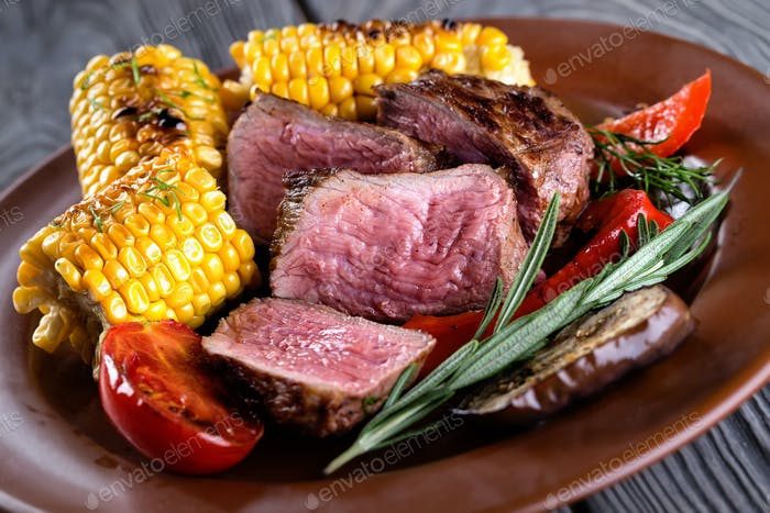 Clay plate with slices of chopped donated meat and corn