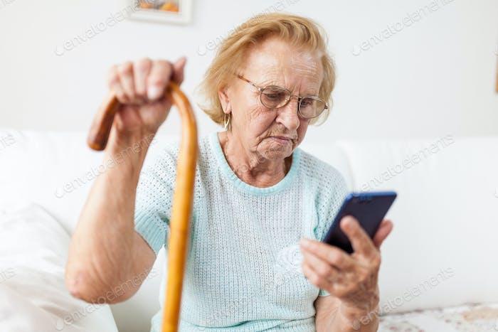 Ältere Frau mit Brille mit einem Mobiltelefon