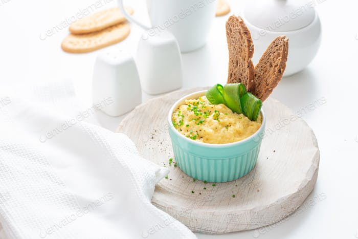 Scrambled eggs with chives and bread, white background