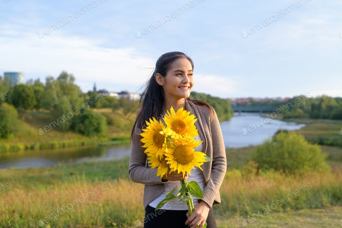 Young happy Asian woman with sunflowers thinking against relaxing view of nature