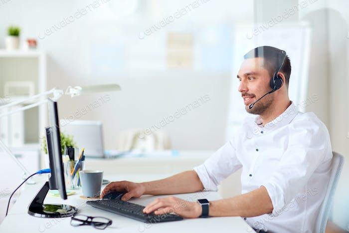 Geschäftsmann mit Headset und Computer im Büro