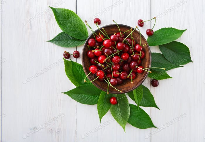 Fresh cherries with green leaves on white wood