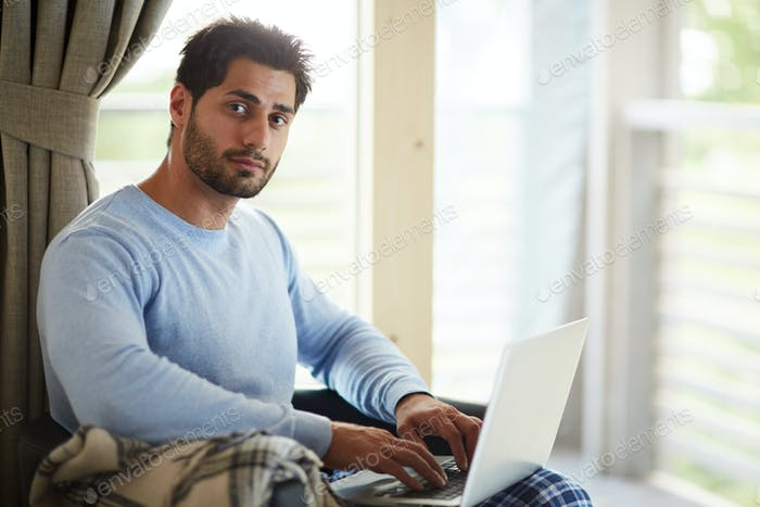 Handsome freelance community manager working at home