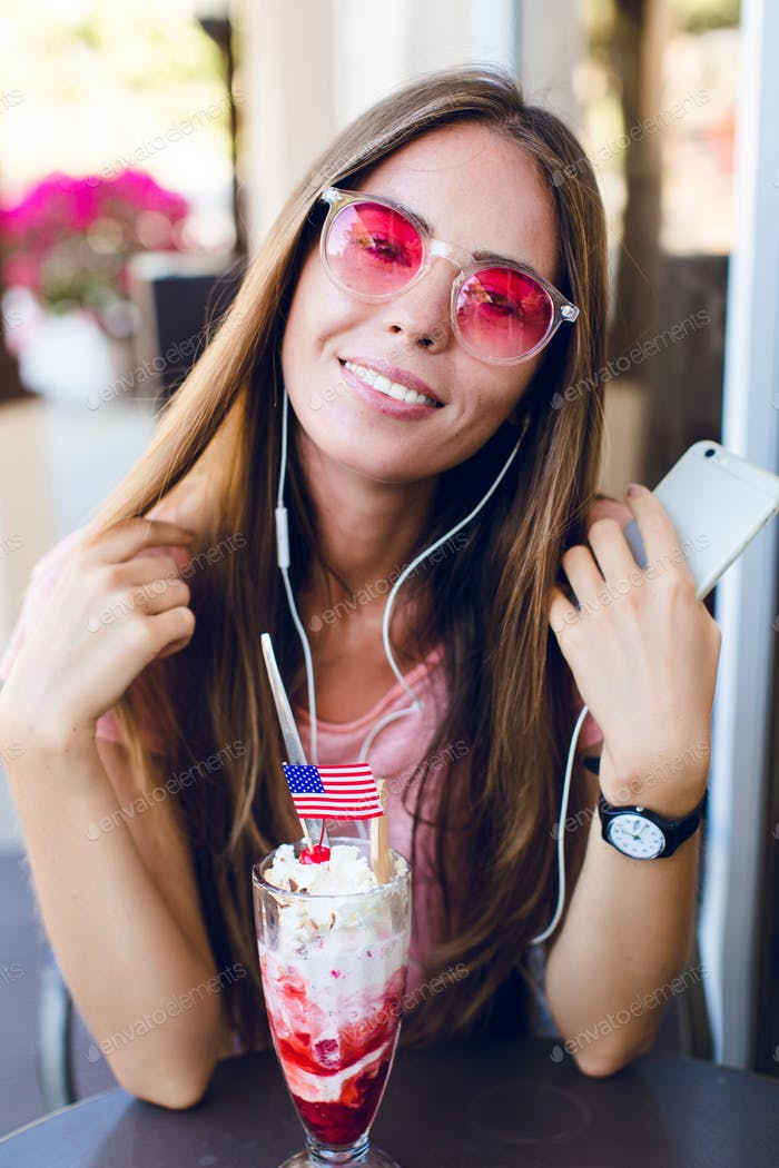 Close-up of cute girl sitting in a cafe eating ice-cream with cherry on top. She wears pink top and