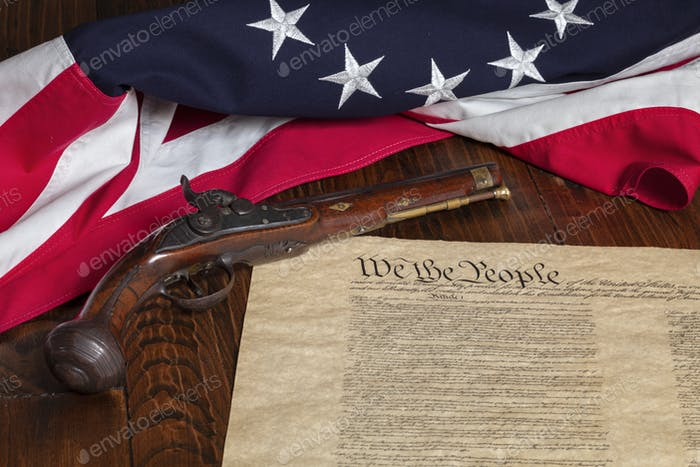 Antique pistol with 13 star flag and the constitution of the United States on dark wood background