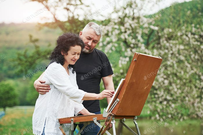 Mature couple have leisure days and working on the paint together in the park