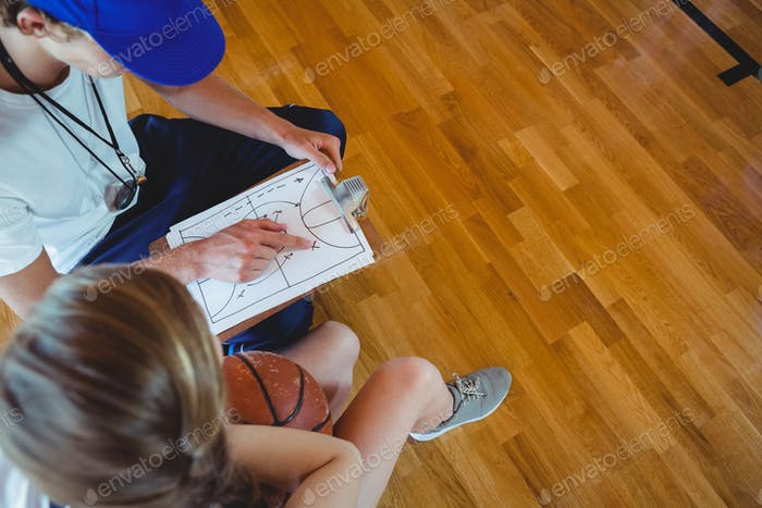 Male coach explaining diagram to female basketball player