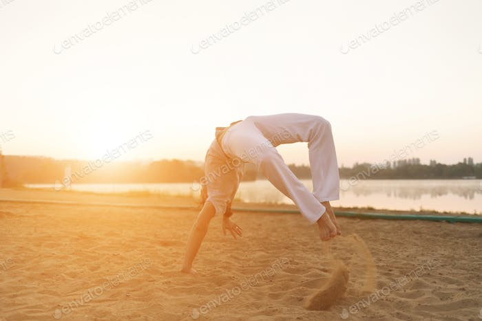 Athletic capoeira performer workout training on the beach sunris