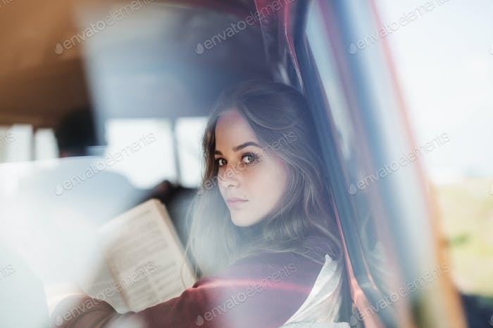 A group of young friends on a roadtrip through countryside, a girl reading a book.