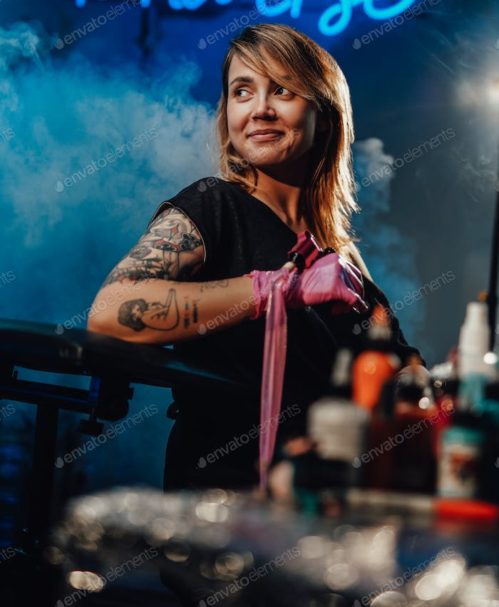 Positive girl and her professional occupation in tattoo salon