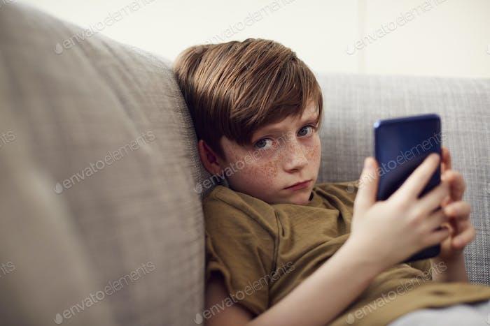 Retrato de chico serio sentado en el sofá en casa juegos en dispositivos de mano en casa