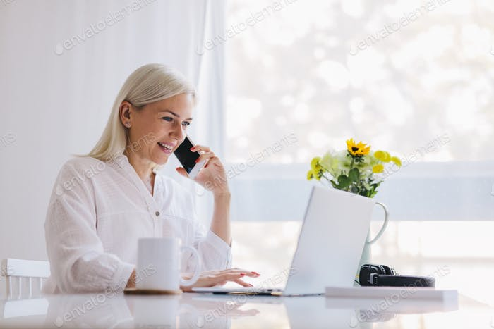 Woman talking on the phone, using laptop.