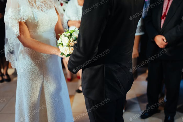 newlywed couple on the wedding day with bouquet in hand