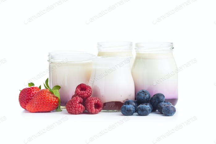 White fruity yogurt in jar and strawberries, blueberries, raspberries
