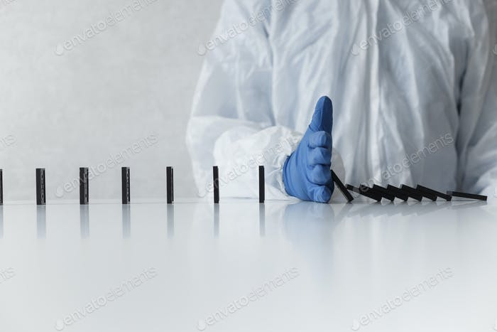 Doctor in protective suit prevent of domino falling by hand in glove