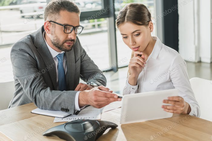 confident businessman and businesswoman looking at tablet together at modern office