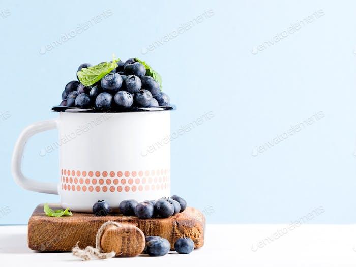 Fresh ripe blueberries in country style enamel mug on rustic wooden board