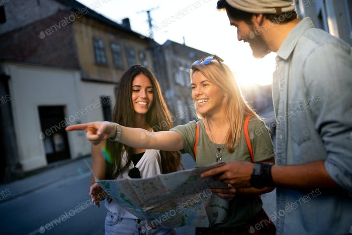 Young happy group of friends sightseeing in city