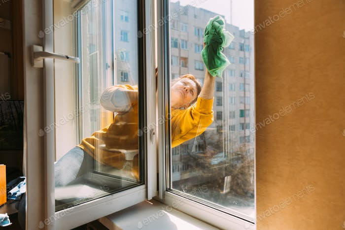 Caucasian Woman Of Fifty In A Yellow Sweater And Jeans Washes A Dusty Window In Apartment. A 50 Year