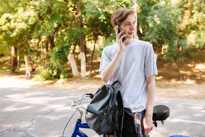 Young man standing with backpack and bicycle and dreamily looking aside talking on his phone