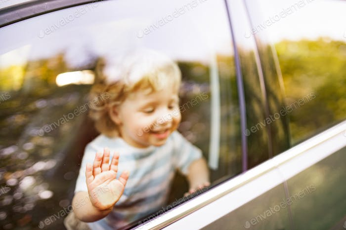 Little boy in the car, looking out of window, waving.