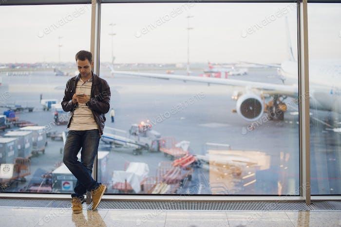 Reisende im Flughafenterminal. Junger Mann mit Handy und wartet auf seinen Flug.