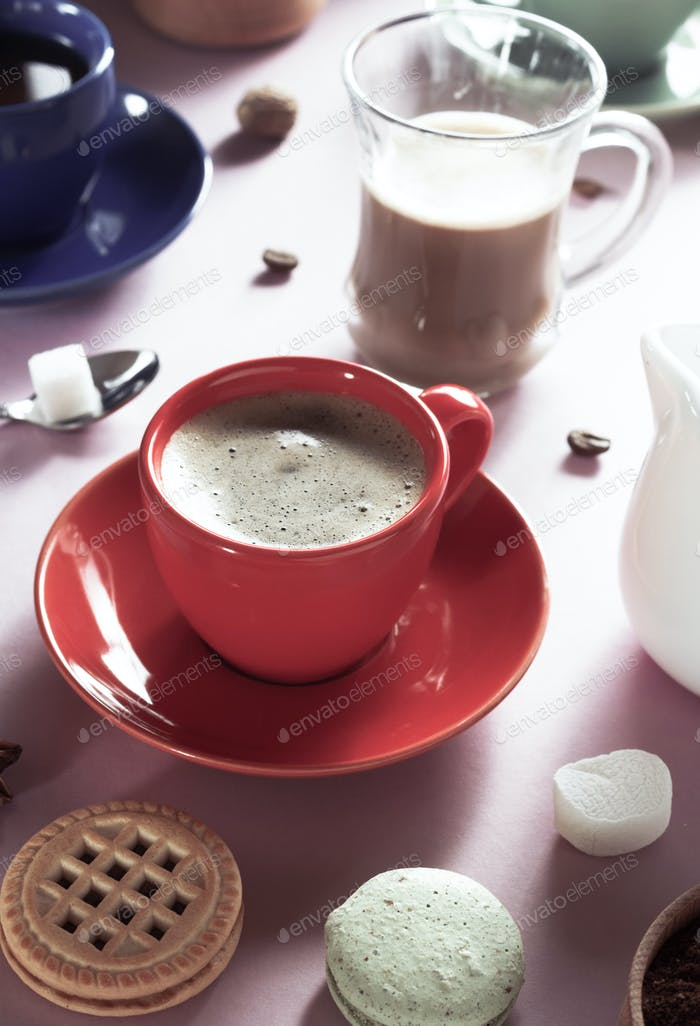 cup of coffee, tea and cacao at purple background