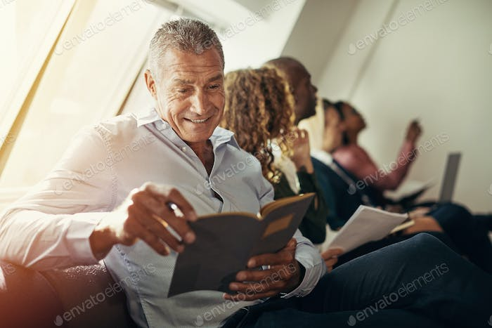 Mature businessman smiling while reading notes during an office presentation