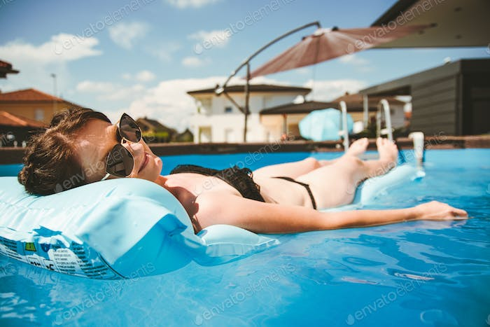 Young woman in bikini on Float Mattress in round above ground swiming pool.