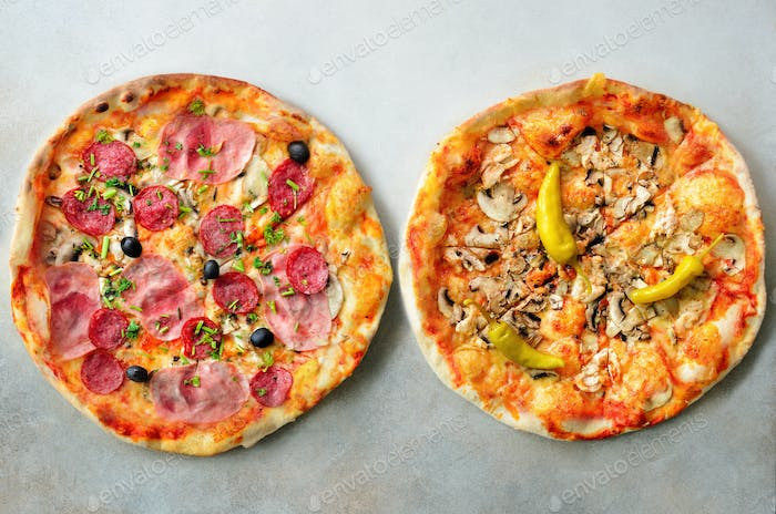 Fresh italian pizza with mushrooms, ham, tomatoes, cheese, olive, pepper on grey concrete background