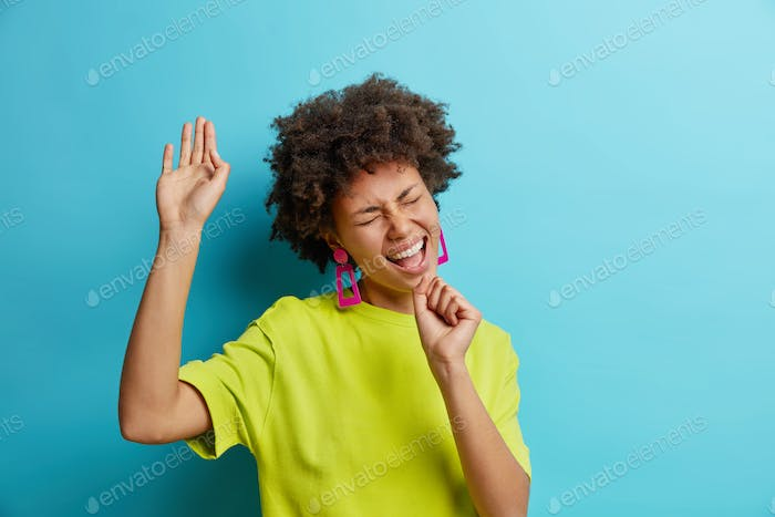 Positive African American woman sings song keeps hand as if microphone has fun has happy mood dresse