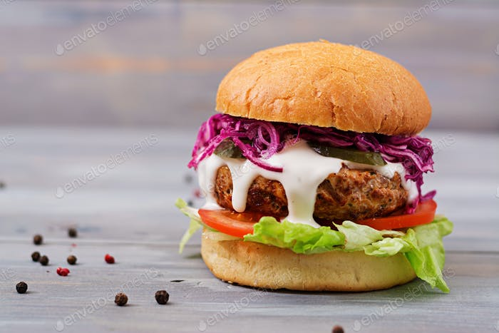 Sandwich hamburger with juicy burgers, tomato and red cabbage