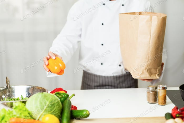 Unrecognizable Chef Unpacking Grocery Shopping Bag In Restaurant Kitchen, Cropped