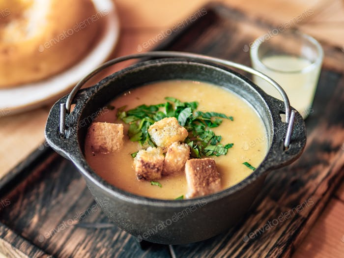 Puree soup with croutons in old metal bowl