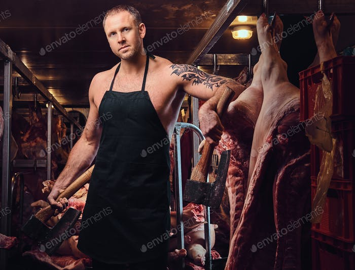 A butcher holds an ax in a meat factory.