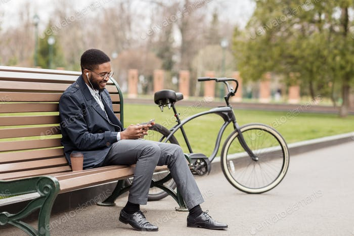 Black man in earphone sitting on bench listening to radio
