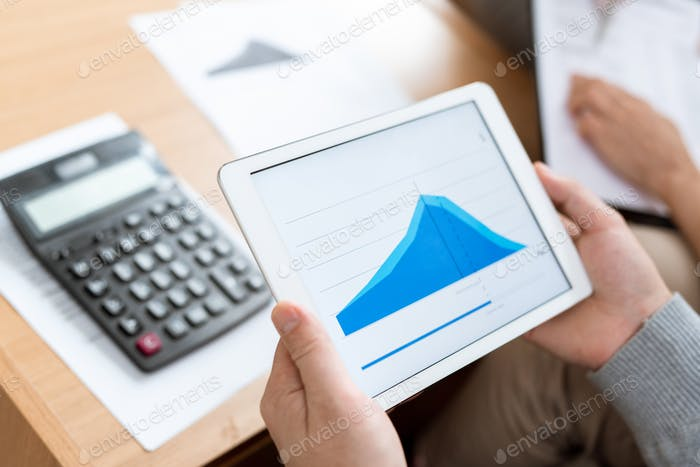 Human hands holding touchpad with blue graph of financial rate on display
