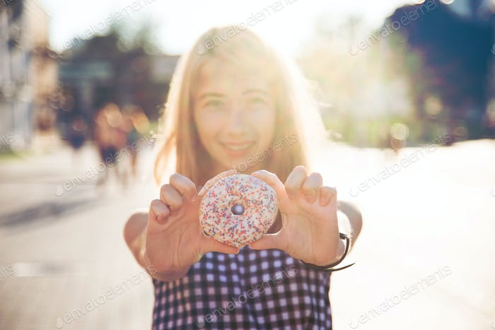 Smiling woman in summer holding donut