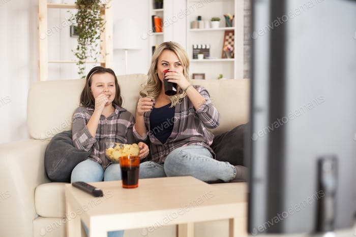 Happy young mother sits on couch with her teenage daughter