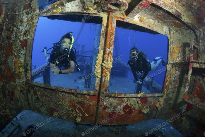 Divers peer through the window frames of the bridge of a shipwreck