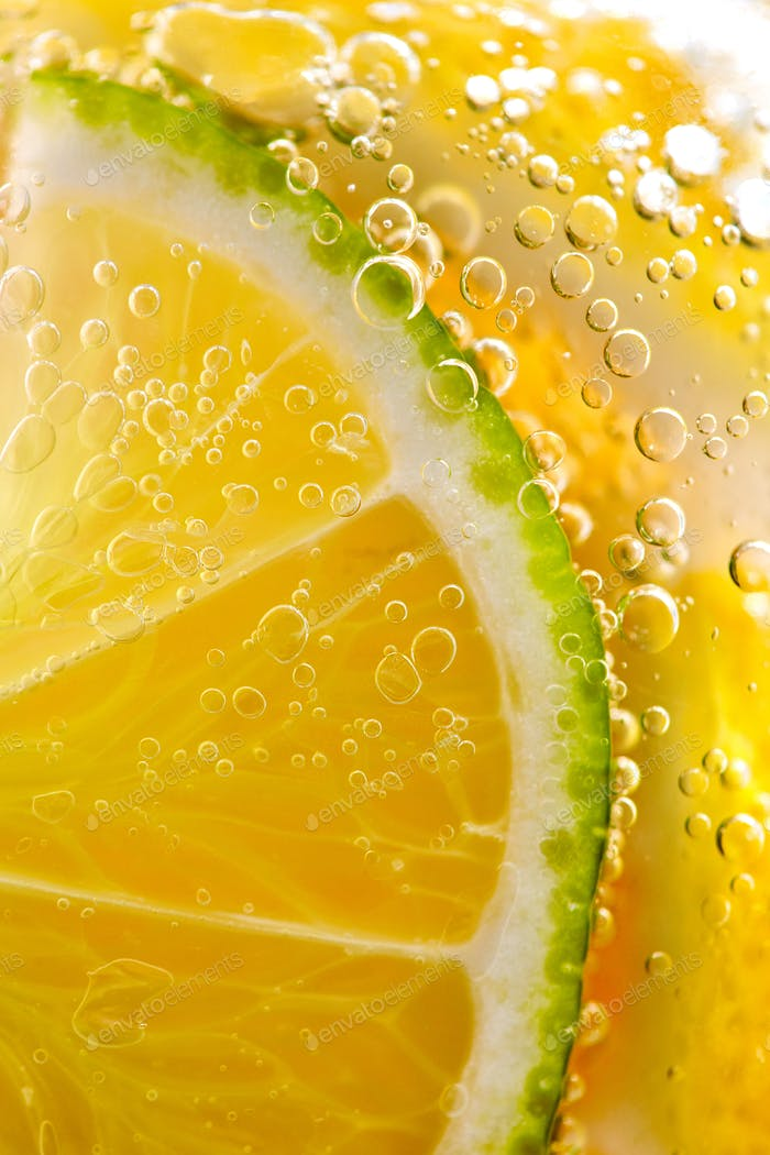 Juicy slices of ripe lemon and lime with bubbles in a glass of water. Macro photo of refreshing