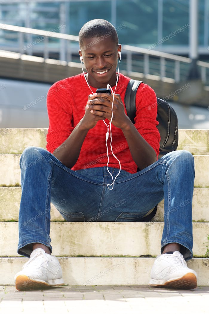 Black male student sitting outdoors and listening  music