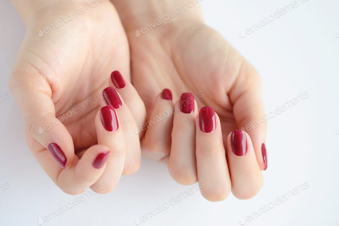Closeup of hands of a young woman with red manicure on nails aga