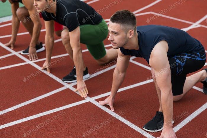 Multiethnische Sportlergruppe bereit zum Laufen