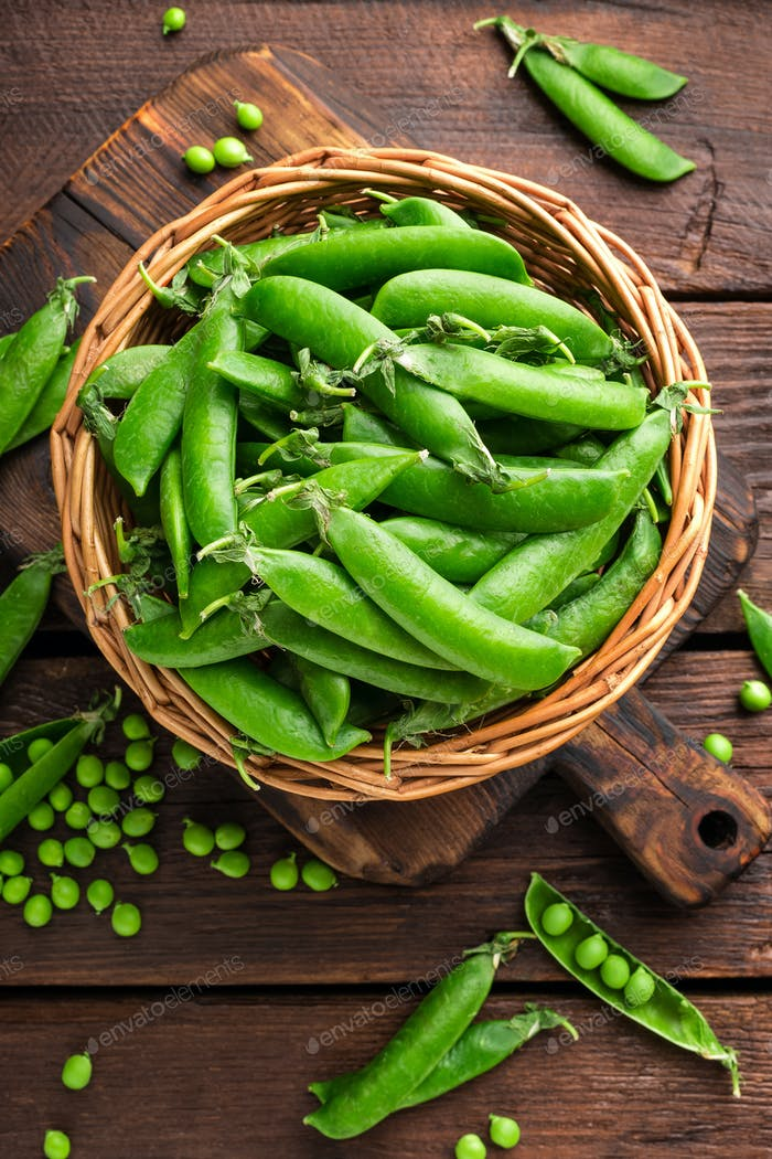 Green peas in pods and peeled in wooden bowl on table