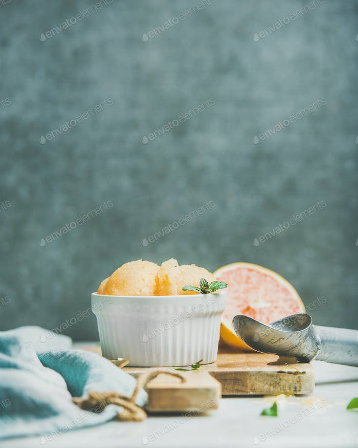 Pink grapefruit sorbet with mint in bowl, copy space