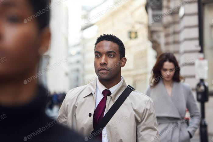 Young black businessman walking in a busy London street looking away, close up