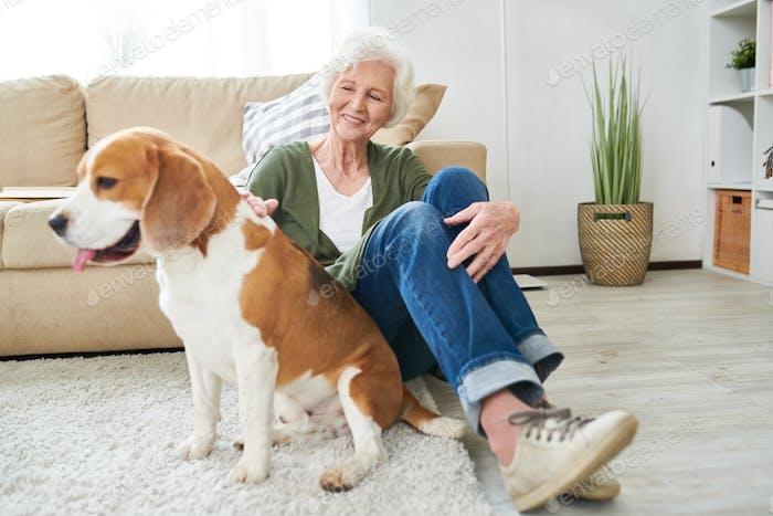 Glückliche Senior Frau spielen mit Hund zu Hause
