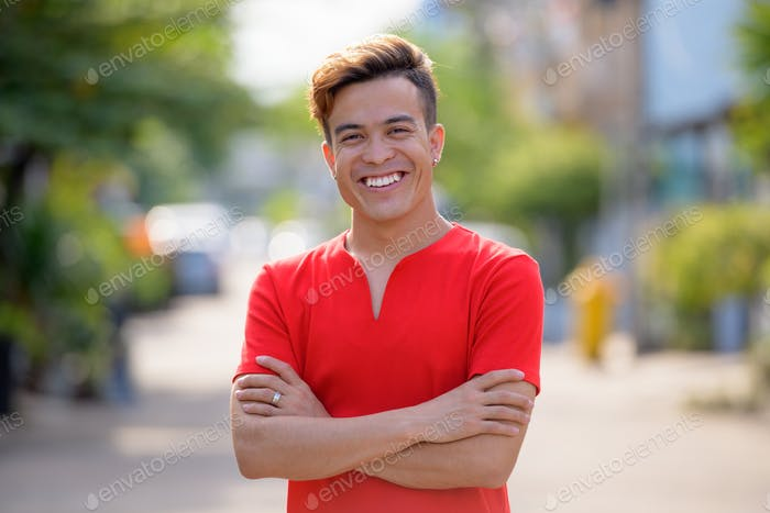 Happy young Asian man smiling with arms crossed outdoors