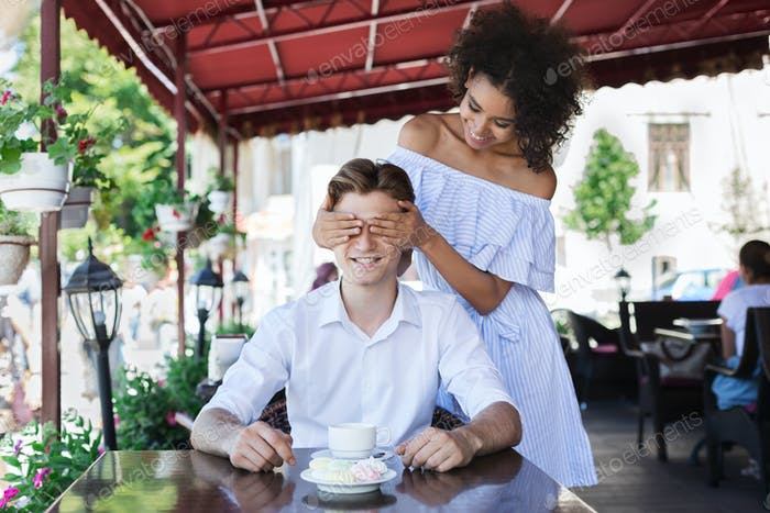 Young woman covering boyfriend eyes in cafe
